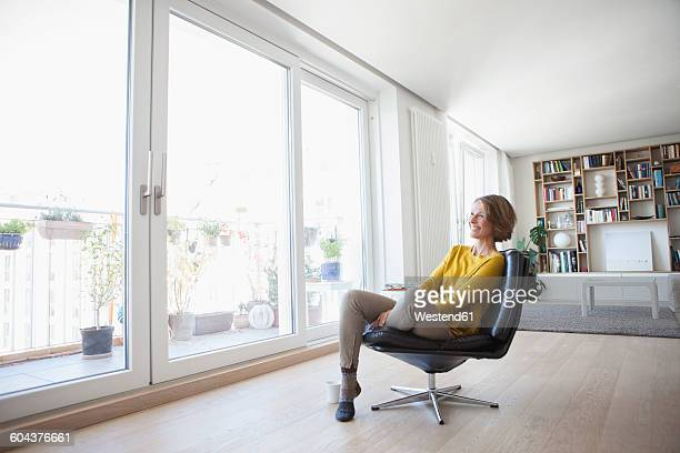 Relaxed woman at home sitting on leather chair