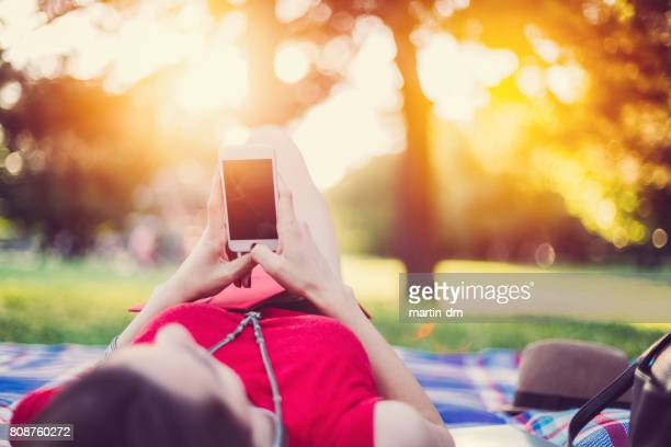 Relaxed woman at picnic using smartphone