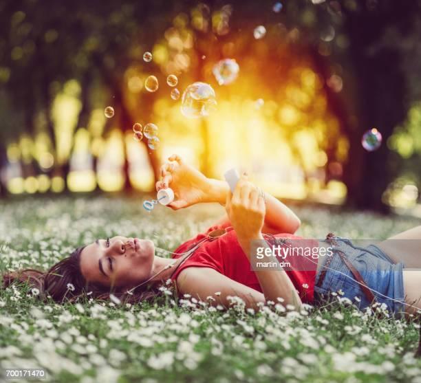 Femme décontractée, soufflant des bulles de savon dans le parc