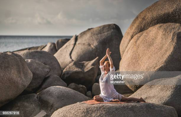 Relaxed woman doing Yoga meditation exercises during summer day on a beach rock.