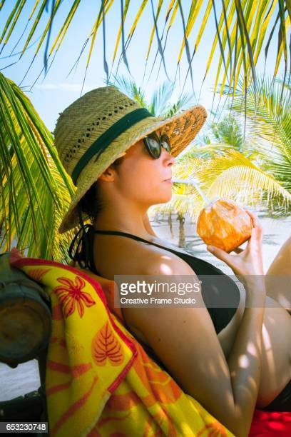 Relaxed woman drinking a coconut with a straw