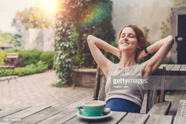 relaxed woman drinking coffee in the garden - serene people stock pictures, royalty-free photos & images