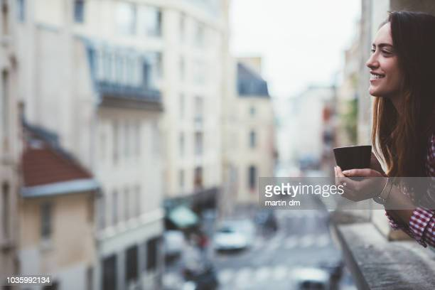 relaxed woman drinking coffee on the window in paris - balcone foto e immagini stock