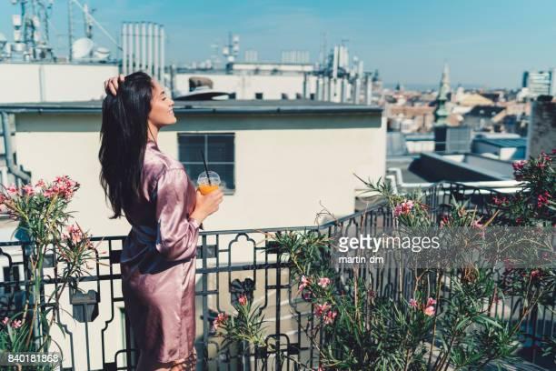 テラスでリラックスした女性 drinkkng オレンジ ジュース - ナイトウェア ストックフォトと画像