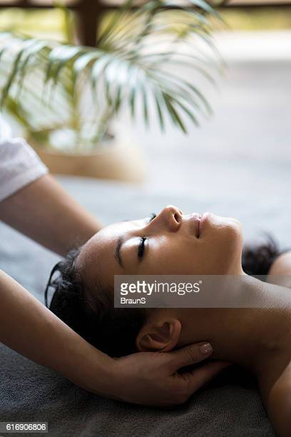 Relaxed woman having her neck massaged at the spa.