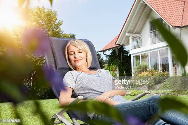 Relaxed woman in deck chair in garden