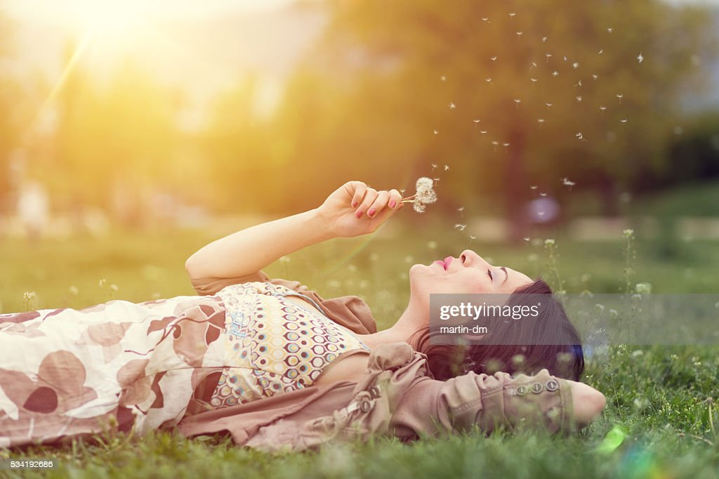 Relaxed woman in the park blowing dandelion : Stock Photo