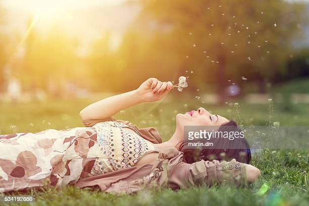 relaxed woman in the park blowing dandelion - tranquility stock pictures, royalty-free photos & images
