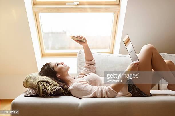 Relaxed woman lying on couch with cell phone and laptop