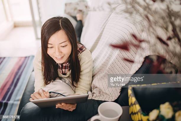 relaxed woman lying on sofa using digital tablet - yiu yu hoi stock pictures, royalty-free photos & images