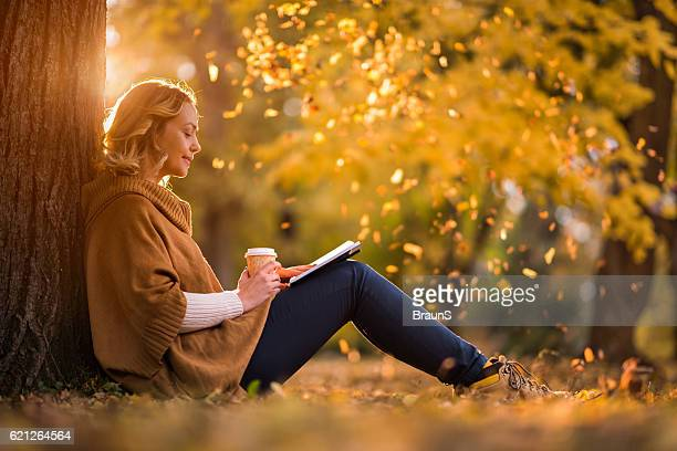 Relaxed woman reading a book in autumn day.