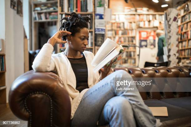 Relaxed woman reading book sitting at bookstore