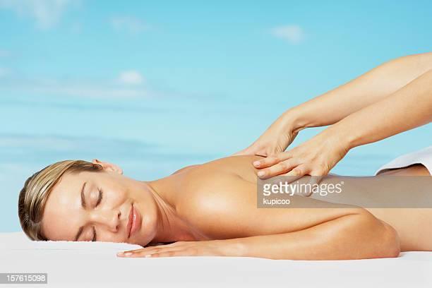 Détendue femme à recevoir un massage du dos contre ciel bleu