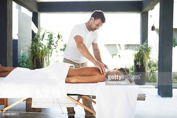 Relaxed woman receiving back massage at spa