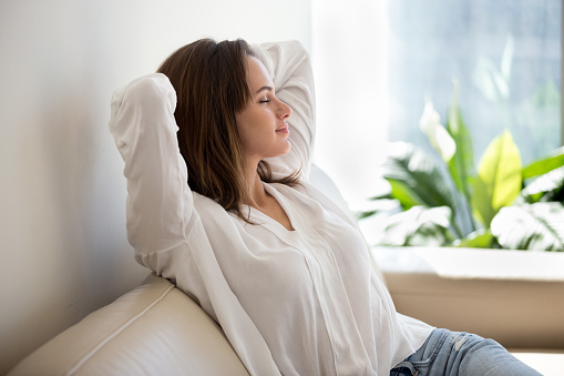 Relaxed woman resting breathing fresh air at home on sofa 994243660
