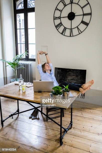 Relaxed woman sitting at desk at home with feet up