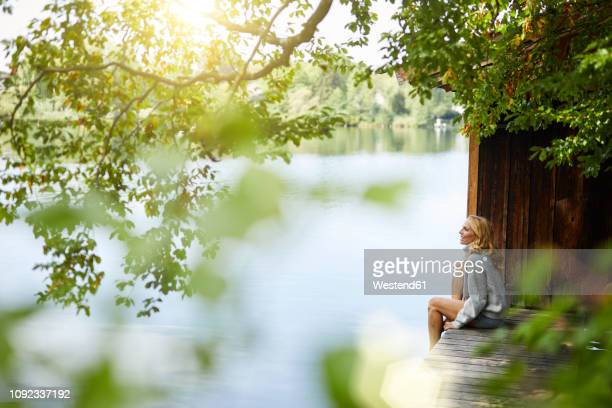 relaxed woman sitting on wooden jetty at a remote lake - adults only stock pictures, royalty-free photos & images