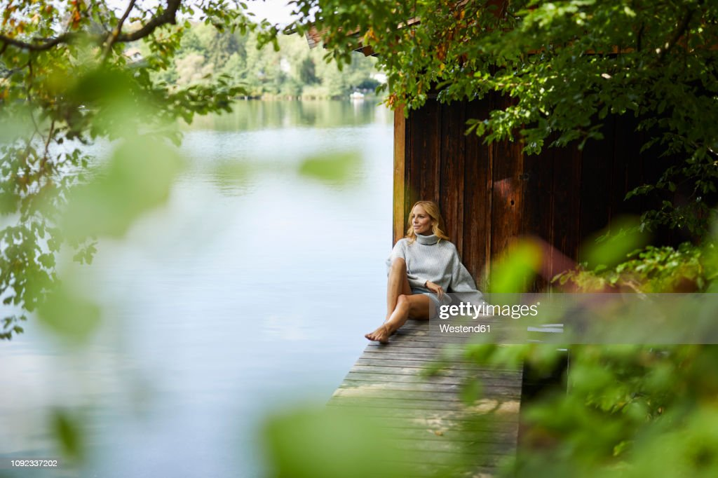 Relaxed woman sitting on wooden jetty at a remote lake : Stock Photo