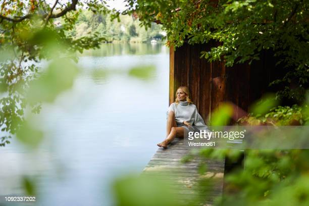 relaxed woman sitting on wooden jetty at a remote lake - rusten stockfoto's en -beelden