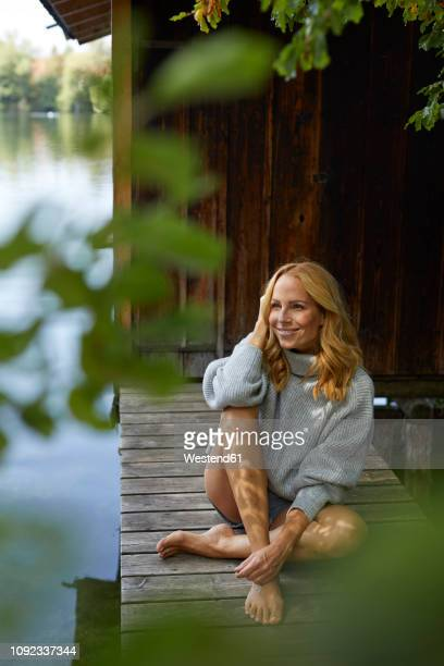 relaxed woman sitting on wooden jetty at a remote lake - blonde long legs stock pictures, royalty-free photos & images