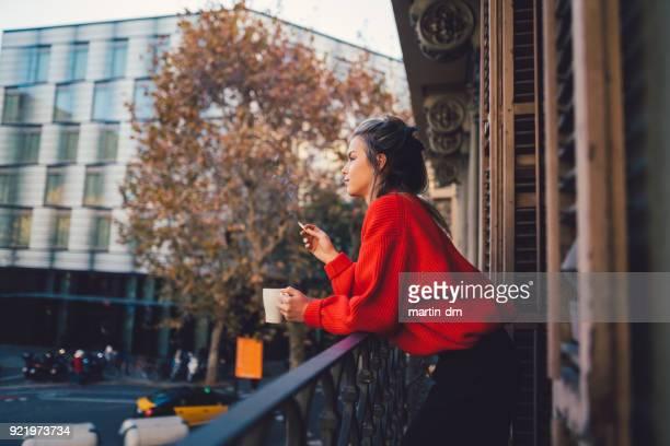 relaxed woman smoking at the terrace - cigarro imagens e fotografias de stock