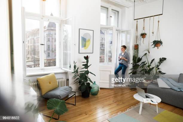relaxed woman standing at the window, drinking coffee - zimmerpflanze stock-fotos und bilder