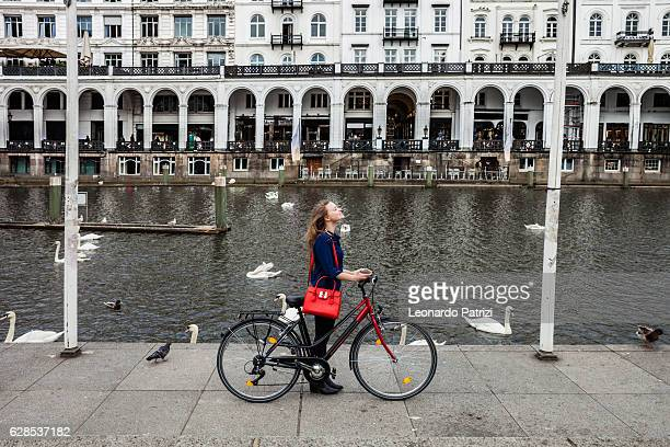 Relaxed woman walking in the city center with bicycle