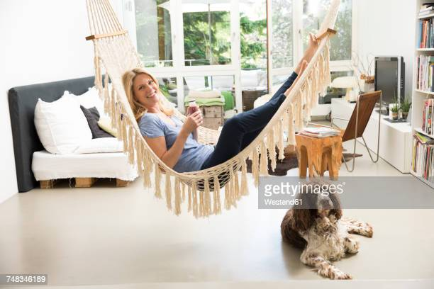 Relaxed woman with dog at home lying in hammock