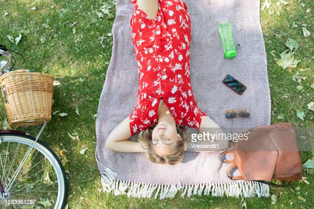 relaxed woman with eyes closed lying on blanket at public park - lying down stock pictures, royalty-free photos & images