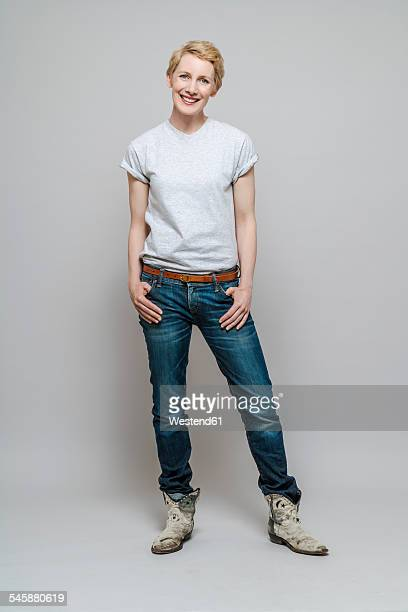 Relaxed woman with hands in her pockets standing in front of grey background