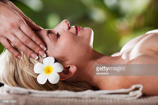 relaxed young adult woman receiving head massage - thai massage stock photos and pictures