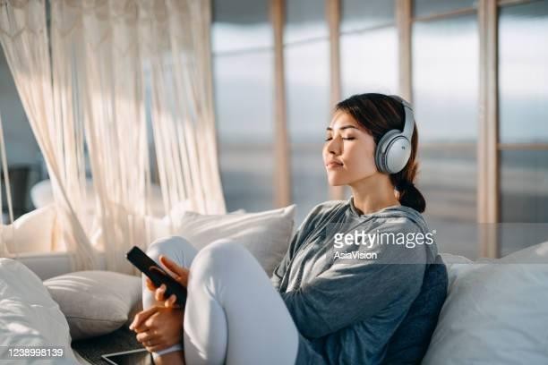 自宅でスマートフォンからヘッドフォンで音楽を楽しんでいる彼女のベッドに座って目を閉じたリラックスした若いアジアの女性 - リラグゼーション ストックフォトと画像