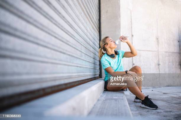 relaxed young blonde athlete drinking from water bottle - roller shutter stock pictures, royalty-free photos & images