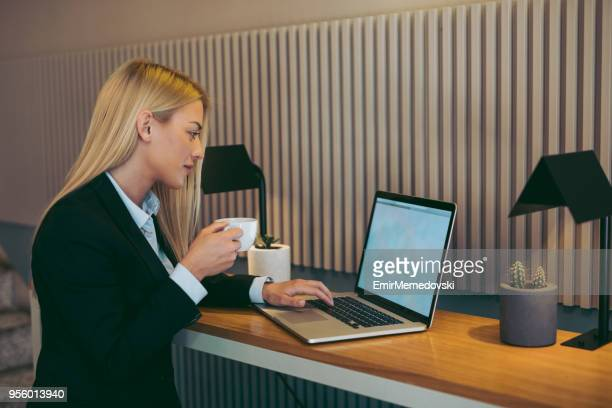 Relaxed young businesswoman having coffee while working on laptop