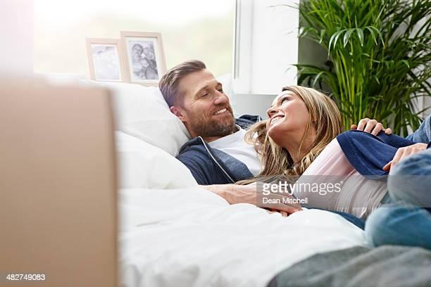 Tranquilo joven pareja acostado de cama