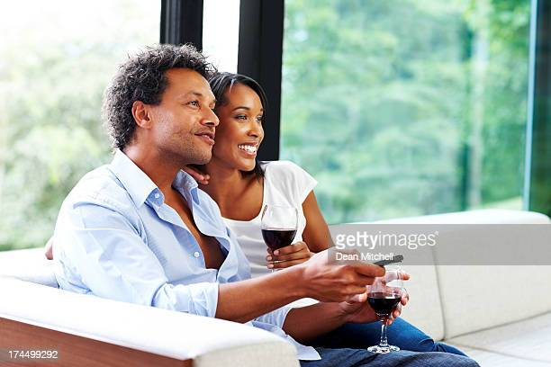 Relaxed young couple watching television