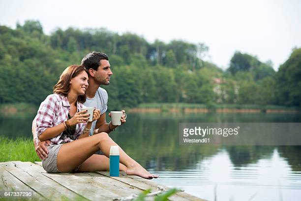 Relaxed young couple with coffee mugs sitting on a jetty at lake looking at distance