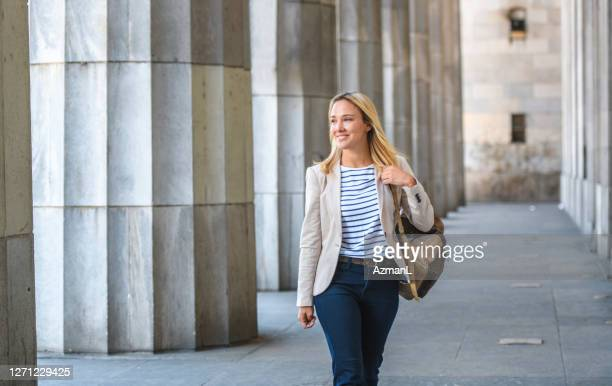 relaxed young law student with backpack walking on campus - approaching stock pictures, royalty-free photos & images