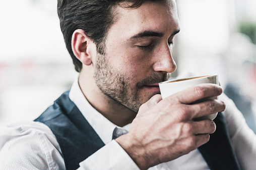 Relaxed young man drinking cup of coffee - gettyimageskorea