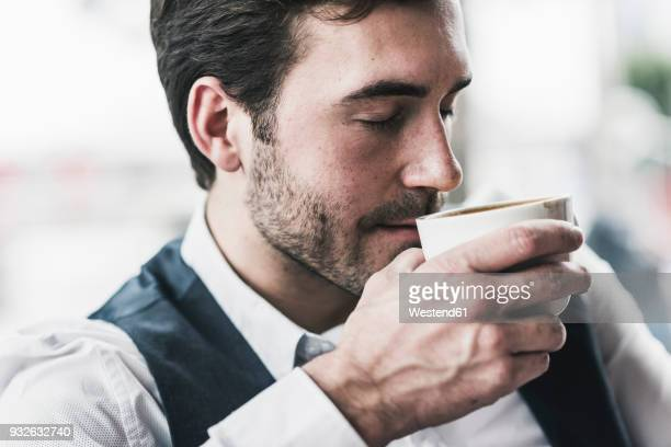 relaxed young man drinking cup of coffee - kaffee getränk stock-fotos und bilder
