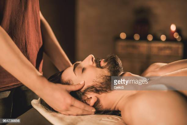 relaxed young man enjoying a head massage side view. - head massage stock photos and pictures
