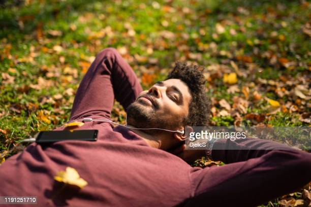 relaxed young man laying on ground and listening to music on autumn day. - tranquility stock pictures, royalty-free photos & images
