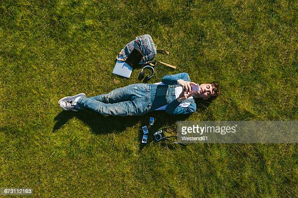 Relaxed young man lying on a meadow using cell phone, top view