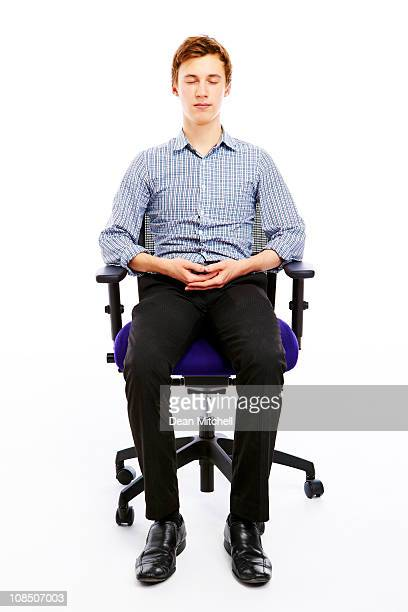 relaxed young man meditation in office chair
