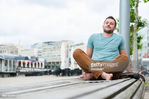 relaxed young man outdoors sitting on bench - ein mann allein stock-fotos und bilder