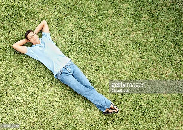 Relaxed young man sleeping on grass