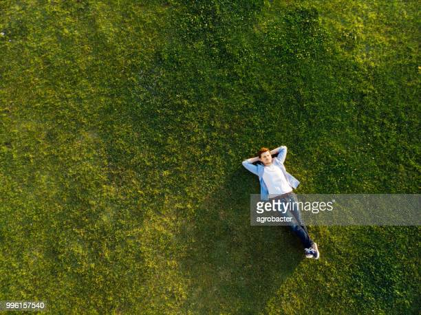 relaxed young man sleeping on grass - lying down foto e immagini stock