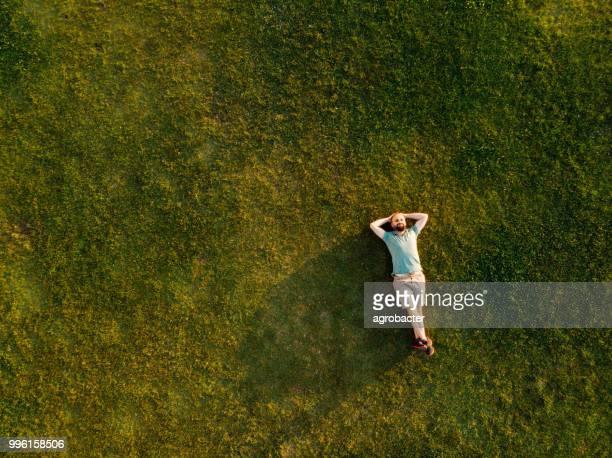 ゆったりした若い男性の芝生寝室