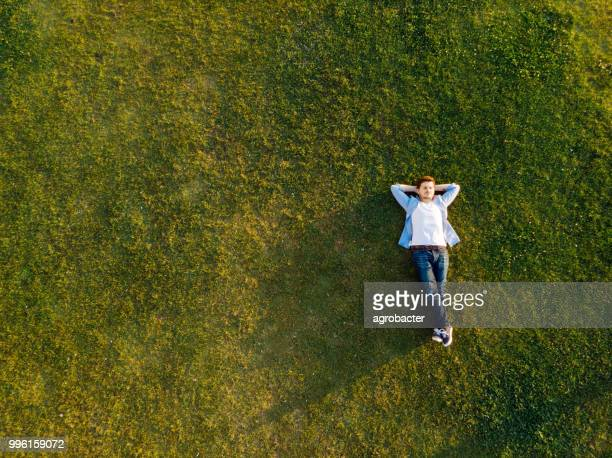 relaxed young man sleeping on grass - lying down stock pictures, royalty-free photos & images