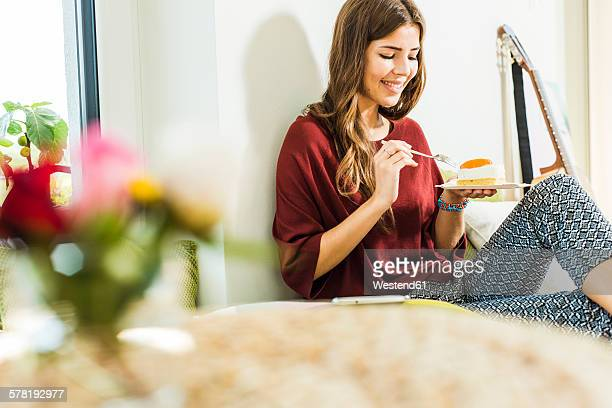 Relaxed young woman at home in bed eating piece of cake